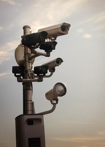 Surveillance cameras against ominous cloudy sky